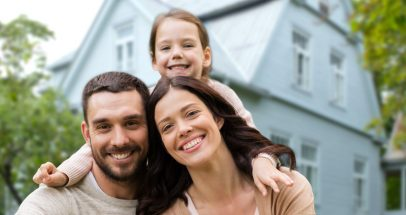 family, real estate and accommodation concept - happy mother, father and little daughter over house background